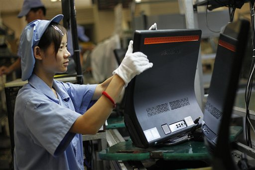 In this photo taken Aug. 11, 2010, a Chinese worker labors at a production line at the factory of Lenovo Electronic Technology Co., Ltd. in Shanghai. Japan lost its place as the world's No. 2 economy to China in the second quarter as receding global growth sapped momentum and stunted a shaky recovery. (AP Photo/Eugene Hoshiko)